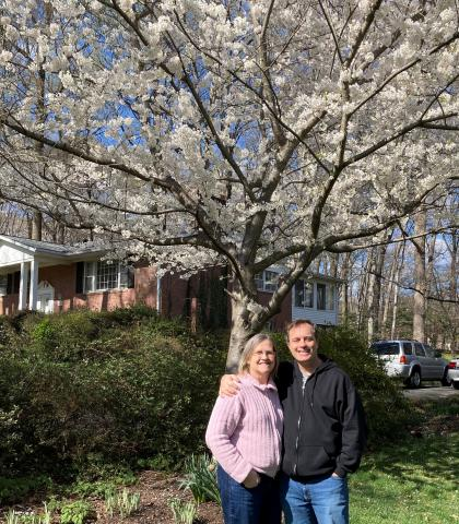Chris and Myke in front of a tree blooming with white flowers