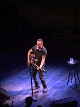 Bruce Springsteen playing guitar on stage.  A stool with a glass of water in the background.