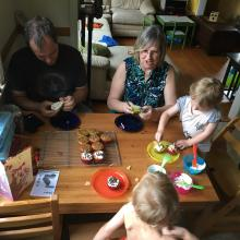 Two children and two adults at a table eating cupcakes